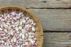 garlic in wicker basket on grunge wooden floor. Royalty Free Stock Image