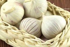 Garlic in wicker basket on straw mat macro Stock Photography