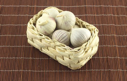 Garlic in wicker basket on straw mat Stock Photos
