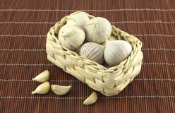 Garlic in wicker basket on straw mat Stock Images