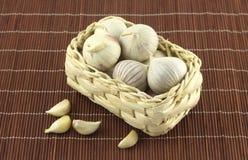 Garlic in wicker basket on straw mat Stock Images