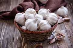 Garlic. In a wicker basket on a vintage table Royalty Free Stock Photo