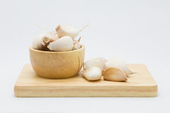Garlic on wooded cup and wooden board. On  white background Royalty Free Stock Images
