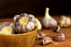 Garlic in a wooden bowl on a kitchen board. Superfood. Traditional folk medicine. Garlic in a wooden bowl on a kitchen board. Superfood. Traditional folk Stock Photography