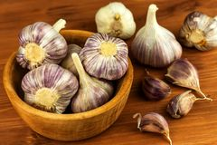 Garlic in a wooden bowl on a kitchen board. Superfood. Traditional folk medicine. Garlic in a wooden bowl on a kitchen board. Superfood. Traditional folk Royalty Free Stock Images