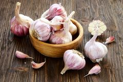 Garlic in a wooden bowl. On the kitchen table Stock Photo
