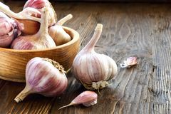 Garlic in a wooden bowl. On the kitchen table Royalty Free Stock Photography