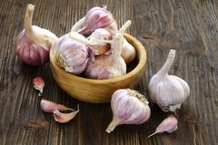 Garlic in a wooden bowl. On the kitchen table Royalty Free Stock Photos