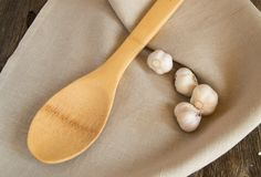 Garlic and a wooden spoon lying on a linen napkin. Old dark farm table, copy space.  Royalty Free Stock Image