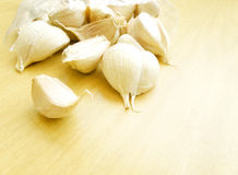 Garlic on wooden table. A high key still life image of some garlic cloves on a wood kitchen table lit by natural sunlight. Bright and well lit. Horizontal color royalty free stock image