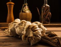 Garlic. On a wooden table with spices, olive oil and vinegar in the background royalty free stock photos