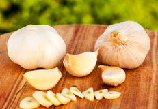 Garlic on wooden table. Whole garlic and cloves on chopping board Royalty Free Stock Photo