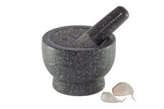 Garlics. Granite mortar and pestle with garlic cloves, isolated royalty free stock photography