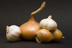 Garlics et oignons sur le fond noir Photographie stock libre de droits