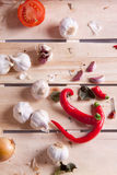 Garlics and peppers on wood Royalty Free Stock Photo