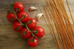 Garluc e spaghetti dei pomodori su un di legno Fotografie Stock