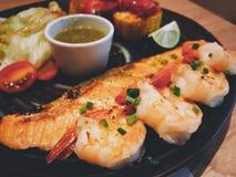 Garnalen en zalmlapje vlees met zeevruchtenonderdompeling het kruiden Stock Foto's