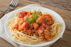 Garnalen in wijntomatensaus over spaghettideegwaren Stock Foto's