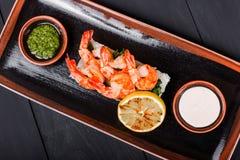 Garnalengarnalen met saus, greens en rijst op zwarte plaat op houten achtergrond worden geroosterd die Heerlijke schotel van zeev stock fotografie