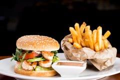 Garnalenhamburger met gebraden gerechten en souce Stock Foto