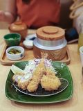 garnalentempura in brand gestoken varkensvlees met kool en citroen op groene plaat royalty-vrije stock foto