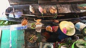 Garnalenzeevruchten het koken op de steenkolen bij het drijven van Bangkok Markt met Kokende Mensen op Boten - Taling Chan Floati stock footage