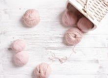 Garnbollar och korg på vit träbakgrund Royaltyfria Bilder