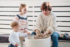 Garncarka rzemieślnik pokazuje małej dziewczynie dlaczego pracować z gliną i ceramicznym kołem Brata dopatrywanie obrazy stock
