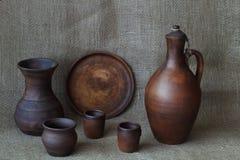 Garncarstwo: gliniany dzbanek dla wina, naczynia, fili?anek, garnka i wazy na szorstkiej domowej roboty jutowej kanwie, Pojęcia â fotografia stock