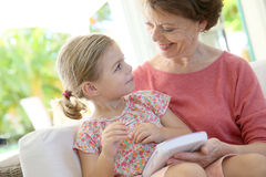 Garndmother and granddaughter playing on tablet stock photo