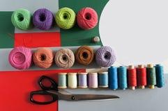 Garne von Threads für das Stricken in den verschiedenen Farben auf einem roten Grün lizenzfreie stockbilder