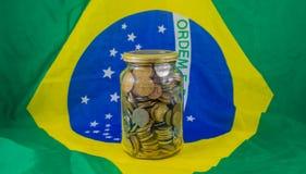Garnek brazylijczyk monety na tło fladze Brazylia, Pieniężna rzeczywistość obrazy royalty free