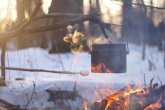 Garnek wrząca woda na ogieniu grże w zima lesie, Zdjęcia Royalty Free