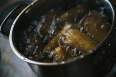 Garnek wypełniał z grulami i wrzącą wodą na kuchence fotografia royalty free