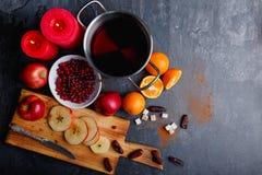 Garnek z kompotem, deska z pokrojonymi jabłkami, cukier, daty, talerz z cranberries i płonące świeczki, Obraz Royalty Free