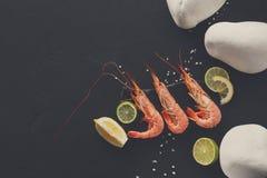 Garnelen mit Zitrone und Steine auf schwarzem Hintergrund Lizenzfreies Stockfoto