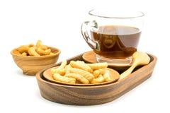 Garnelencracker und eine Schale schwarzer Kaffee in einem hölzernen Behälter mit sa Lizenzfreie Stockbilder