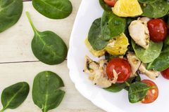 Garnerat med klippt fetasallad från spenat, höna, körsbärsröda tomater och apelsinen Arkivfoto