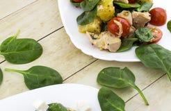 Garnerat med klippt fetasallad från spenat, höna, körsbärsröda tomater och apelsinen Arkivfoton