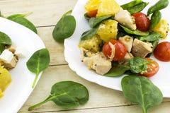 Garnerat med klippt fetasallad från spenat, höna, körsbärsröda tomater och apelsinen Arkivbild