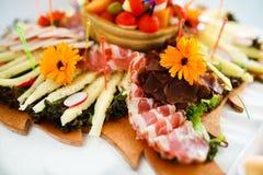Garnering av kött och ost på plattan royaltyfri foto