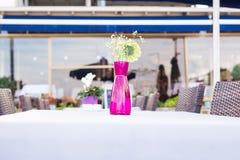 Garnering av nya blommor på tabellen i utomhus- restaurang Royaltyfri Foto