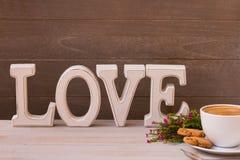 Garnering för dag för valentin` s Kopp kaffe, blommor och ordförälskelse på träbakgrund arkivbild