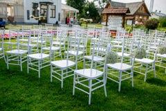Garnering för gifta sig ceremoni för sommar utomhus- Vita klassiska stolar som hyser gäster på ceremonin Bollgypsophilagarnering arkivfoto