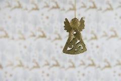 Garnering för jul för julfotografibilden som hänger upp av guld, blänker ängel med bakgrund för reninpackningspapper royaltyfria foton