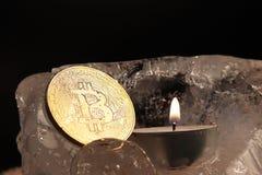 Garnering för ` s för nytt år Bitcoin som sjunkas in i isen och ljusnas av flamman av en stearinljus mot bakgrunden av julgranen royaltyfri fotografi