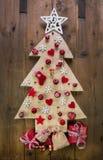 Garnering: handgjort snidit julträd med röda miniatyrer arkivbild