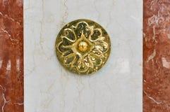Garnering i formen av en blomma på en marmortjock skiva Volymetrisk, skinande, sniden härlig gravyr på enbrunt stenvägg royaltyfria bilder