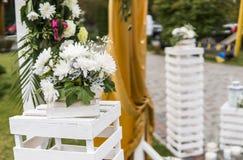 Garnering på ett bröllop Blom- träbåge med den gula torkduken och nya vita blommor med gröna sidor på ett lantligt fotografering för bildbyråer