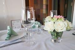 Garnering som äter middag tabellen med blomma- och exponeringsglasvin Arkivfoto
